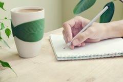 La mano de una mujer con el lápiz se escribe en diario con espirales Al lado a la tabla está la taza de café y de planta con las  Fotografía de archivo