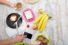 La mano de una mujer con la comida y el teléfono Fotografía de archivo