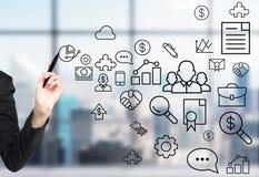 La mano de una mujer está dibujando algunos iconos del negocio en la pantalla de cristal Oficina panorámica moderna con la opinió Imagen de archivo libre de regalías