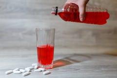La mano de una mujer vierte los deportes rojos bebe o limonada en una taza de cristal de una botella plástica Bebida de la energí Fotos de archivo