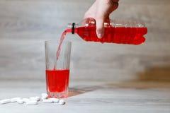 La mano de una mujer vierte los deportes rojos bebe o limonada en una taza de cristal de una botella plástica Bebida de la energí Imágenes de archivo libres de regalías