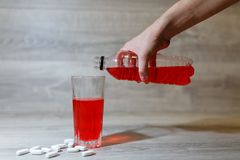 La mano de una mujer vierte los deportes rojos bebe o limonada en una taza de cristal de una botella plástica Bebida de la energí Foto de archivo libre de regalías