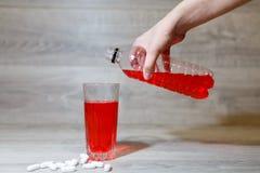 La mano de una mujer vierte los deportes rojos bebe o limonada en una taza de cristal de una botella plástica Bebida de la energí Imagen de archivo libre de regalías
