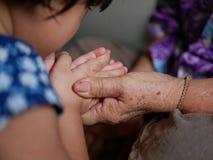 La mano de una persona mayor que lleva a cabo las manos de un pequeño bebé mientras que el bebé que hace el wai, pagando respe fotografía de archivo libre de regalías