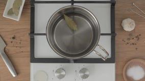 La mano de la visión superior pone la hoja de laurel en cacerola del metal con agua en estufa metrajes