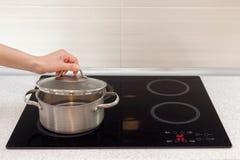 La mano de Woomen abre un cazo en cocina moderna con la estufa de la inducción Fotografía de archivo