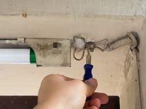 La mano degli elettricisti tiene un cacciavite Provare sistema leggero fotografia stock libera da diritti