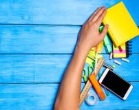 la mano degli studenti della scuola pulisce via i rifornimenti di scuola sul fondo di legno blu della tavola lo studente preferis Fotografie Stock