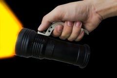 La mano degli uomini che tiene una torcia elettrica su fondo Immagine Stock Libera da Diritti