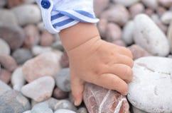 La mano dei bambini tiene una pietra Fotografie Stock