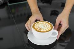 La mano dei camerieri dà il cappuccino Immagine Stock