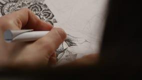 La mano del artista dibuja una pluma almacen de metraje de vídeo