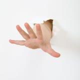 La mano del bambino attacca fuori dal foro Fotografie Stock