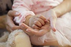 La mano del bambino della tenuta della madre Fotografia Stock