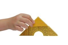 La mano del bambino fa una costruzione con i blocchetti del yelloow Fotografia Stock