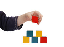La mano del bambino fa una costruzione dei blocchi colorati Fotografie Stock Libere da Diritti