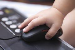 La mano del bambino facendo uso del topo del computer Immagine Stock