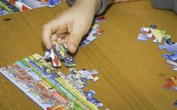 La mano del bambino monta il puzzle sulla tavola fotografie stock