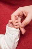 La mano del bebé con el dedo de la mamá Foto de archivo libre de regalías