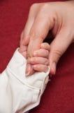 La mano del bebé con el dedo de la mamá Fotografía de archivo