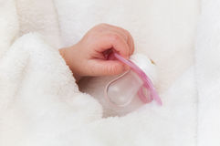 La mano del bebé con el maniquí rosado Imagen de archivo libre de regalías