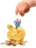 La mano del bebé con la moneda y el piggybank. Foto de archivo