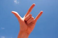 La mano del claxon firma encima el fondo del cielo azul Fotos de archivo libres de regalías