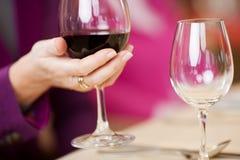 La mano del cliente que sostiene la copa de vino en la tabla del restaurante Foto de archivo libre de regalías