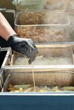 La mano del cocinero comprueba la calidad de patatas fritas Patatas fritas fritas en aceite de ebullici?n en una sart?n fotografía de archivo