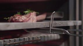 La mano del cocinero en guante negro pone el pedazo de carne con la costilla en horno usando cierre de la herramienta del metal p almacen de video