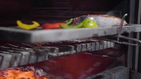 La mano del cocinero en guante negro pone el pedazo de salmones con las verduras en horno usando cierre de la herramienta del met metrajes