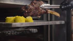 La mano del cocinero en guante negro toma hacia fuera el pedazo del juicie de carne con la costilla del horno usando las pinzas s metrajes