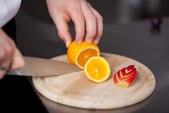 La mano del cocinero que corta la naranja para adornar Imagen de archivo libre de regalías