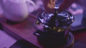 La mano del cocinero que cubre la sopa sabrosa con las setas y los tallarines en el cuenco del metal con una tapa en la tabla en  metrajes