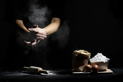 La mano del cocinero trilla la harina con el rodillo y los ingredientes de madera Fotografía de archivo libre de regalías