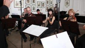 La mano del conductor y de la orquesta sinfónica, violinistas con las notas juega en sus instrumentos musicales dentro metrajes
