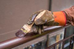 La mano del contratista con el cepillo que construcción que cerca con barandilla del metal de la pintura imágenes de archivo libres de regalías