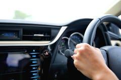 La mano del control de la mujer la rueda de control y conduce el coche imagen de archivo