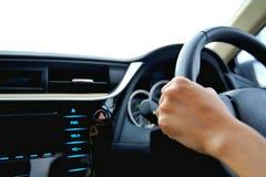 La mano del control de la mujer la rueda de control y conduce el coche foto de archivo