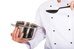 La mano del cuoco unico che tiene il vaso ed il cucchiaio dell'acciaio inossidabile Fotografie Stock