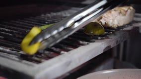 La mano del cuoco unico prende le verdure dalla griglia e le mette sul piatto facendo uso delle tenaglie si chiude su Pepe e limo video d archivio