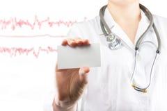 La mano del doctor de sexo femenino que sostiene la tarjeta de visita en blanco Ciérrese encima de tiro en fondo borroso médico C Fotografía de archivo libre de regalías