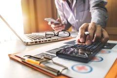 La mano del doctor elegante utilizó una calculadora y una tableta para los costes médicos fotografía de archivo