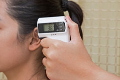 La mano del doctor que comprueba el oído de la mujer con el termómetro digital infrarrojo fotos de archivo