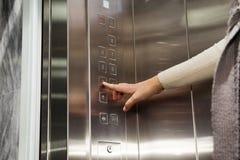 La mano del elevador hace clic en los pisos del botón Foto de archivo