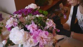 La mano del fiorista fa i fiori dei mazzi in vaso grigio archivi video