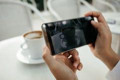 La mano del fondo della tecnologia e dell'alimento dell'uomo d'affari tiene il cellulare p Immagine Stock