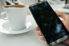 La mano del fondo della tecnologia e dell'alimento dell'uomo d'affari tiene il cellulare p Fotografia Stock