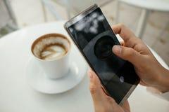 La mano del fondo della tecnologia e dell'alimento dell'uomo d'affari tiene il cellulare p Fotografie Stock