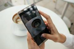 La mano del fondo della tecnologia e dell'alimento dell'uomo d'affari tiene il cellulare p Immagini Stock